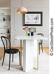 Black chair at table with flowers in white dining room interior with poster and lamp. Real photo