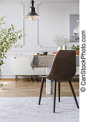 Black chair on grey carpet at table in dining room interior with lamp and wall with molding. Real photo
