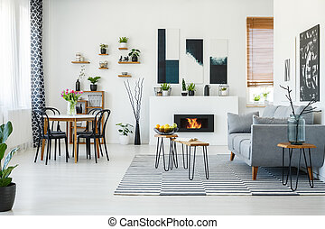 Black chairs at dining table in bright living room interior...