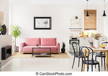 Black chairs at dining table in white flat interior with kitchenette and posters above couch. Real photo