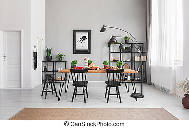 Black chairs at dining table with food in apartment interior with lamp and poster on grey wall. Real photo