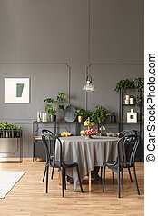 Black chairs at round table under lamp in grey dining room interior with poster and plants. Real photo