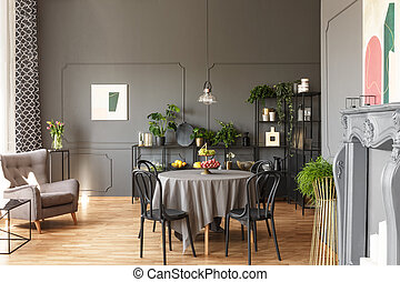 Black chairs at round table under lamp in grey loft interior...
