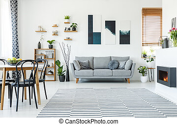 Black chairs at table in spacious apartment interior with posters above grey sofa. Real photo