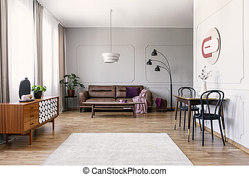 Black chairs at table near wooden cabinet in vintage living room interior with leather sofa. Real photo