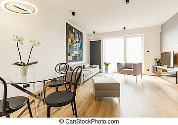 Black chairs at table with flowers in spacious apartment interior with sofa and armchair. Real photo