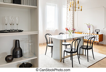 Black chairs at table with flowers under gold lamp in white modern dining room interior. Real photo