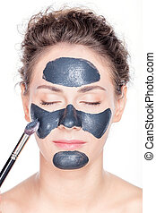 Black charcoal mask application on beautiful woman. - Young...