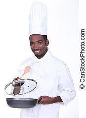 black chef holding pan