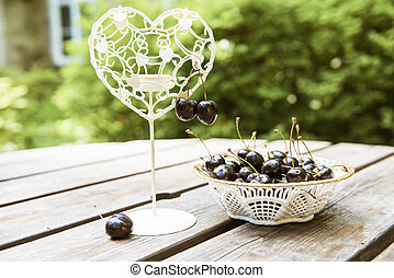 Black cherries berries in a white plate on the wooden table