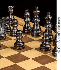 Black chess pieces on a board ready to play a game