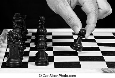 Black chess pieces with hand playing
