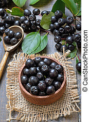 Black chokeberry in wooden bowl