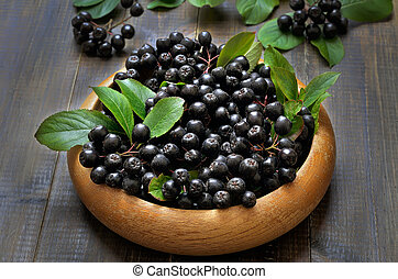 Black chokeberry in wooden plate, close up
