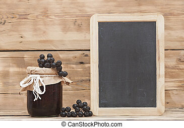 Black chokeberry jam on wooden table