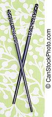 Black Chopsticks on Green Patterned Background