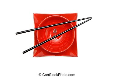 Black chopsticks on two red and black Japanese bowls and square plate isolated