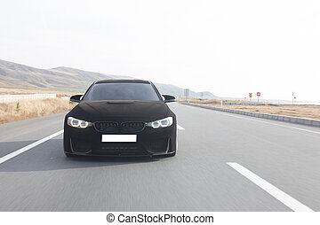 Black chrome luxury sport car driving on the road