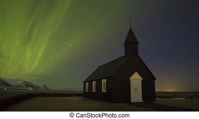 Black church of Budir with northern lights in Iceland,...