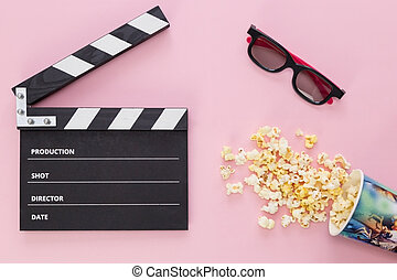 black clapperboard and popcorn isolated on pink background