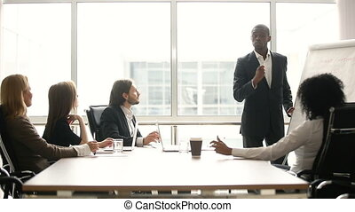 Black coach giving presentation for businesspeople in office with flipchart
