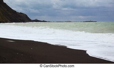 Black coarse sand on the shore of the mountain stormy sea -...