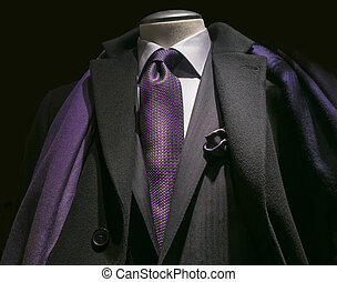 Close-up of a black coat, black jacket, white shirt, purple tie and scarf.