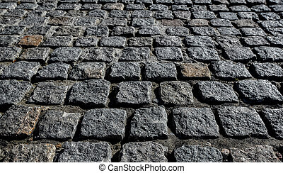 Black cobbled stone road background. Black or dark grey stone pavement texture. Ancient paving stone background