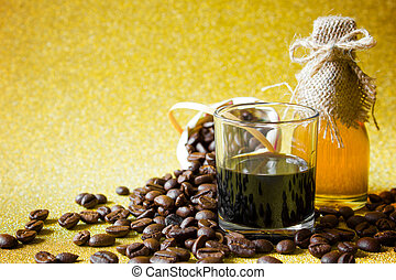 Black coffee cup and Coffee beans and Honey in the bottleon on golden background.