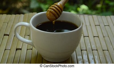 black coffee filling honey from wooden scoop on bamboo...