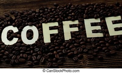 Black coffee grains lie on a brown wooden table. The word coffee
