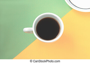 Black coffee in a white cup on green and yellow background