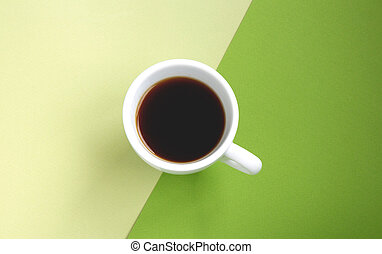 Black coffee in a white cup on green background