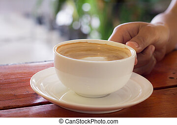 Black coffee in the white cup on the wooden table. Woman hand holding a cup of coffee.