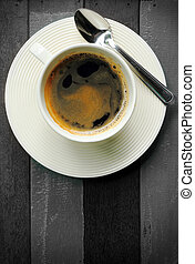 black coffee in white cup on black and white wood background.