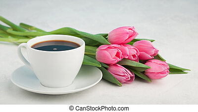 Black coffee in white Cup with pink tulips on light stone...