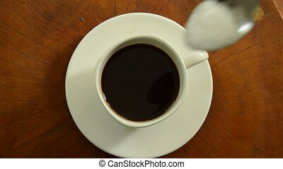 black coffee mixed with sugar in cup