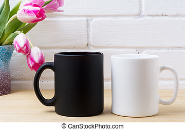 Black coffee mug and white cappuccino cup mockup with pink...