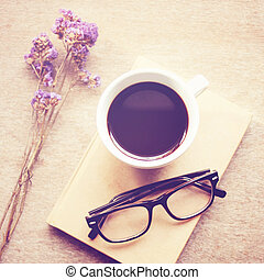 Black coffee on notebook with eyeglasses, retro filter effect