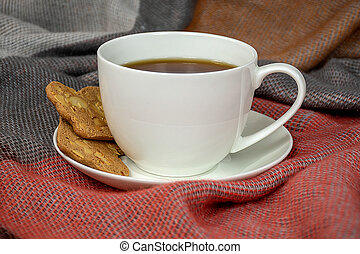 black coffee with cookies on blanket