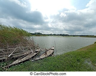 black colored wooden boat on lake