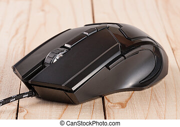 black computer mouse on a light wooden background closeup