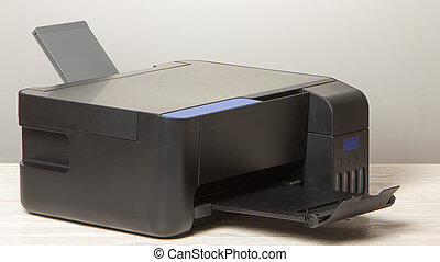 Black copier on white wooden table, closeup.