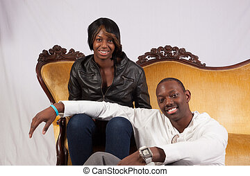 Black couple, man and woman sitting on a gold couch smiling at the camera