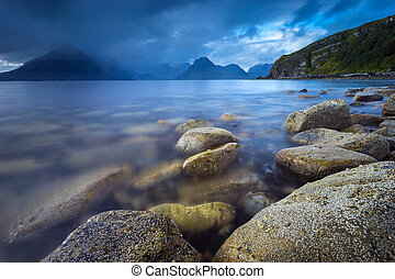 Black Cuillins mountain ridge viewed from Elgol coastline with dramatic sky