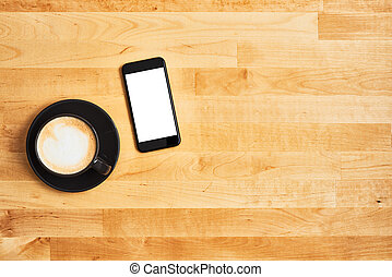 Black cup of coffee with black smartphone on wooden table