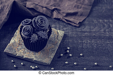 Black cupcakes on a wooden background