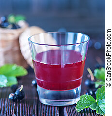 black currant juice in glass and on a table