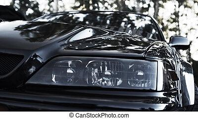 Black custom sports car headlight close up front view.
