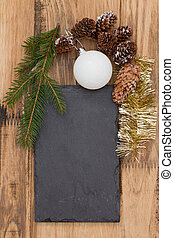 black cutting board with Christmas decoration on brown wooden background